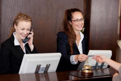 """Bild zum Thema """"Mitarbeiter-Coaching"""", 2 gepfelgte freundliche Mitarbeiterinnen am Empfang eines Hotels"""