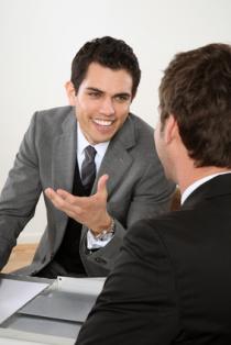 Bild zum Thema Kommunikationsfähigkeit und Erfolgsfaktoren, 2 Geschäftsmänner mit positiver Ausstrahlung im Gespräch