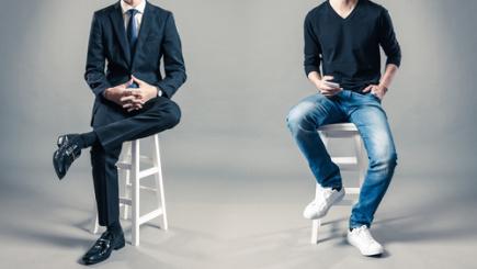 Foto zum Thema Imagegestaltung-Entfaltung, 2 Männer auf Hockern (Kopf nicht zu sehen - einer im Anzug, der andere in Jeans und schwarzem t-Shirt